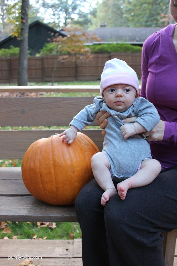 babys-first-halloween-sitting-by-pumpkin