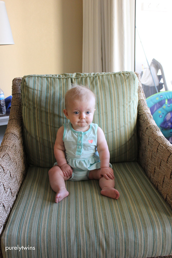 8 month old baby girl sitting on chair for monthly picture updates purelytwins