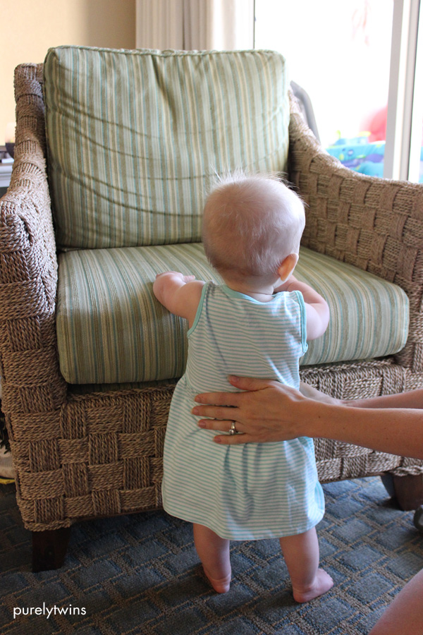 8 month old baby girl holding on to a chair to practice standing