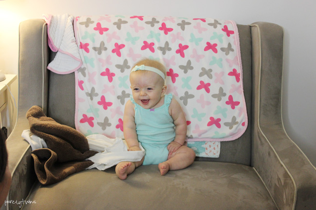 9 month old baby girl sitting in chair for her 9 month update. purelytwins.com