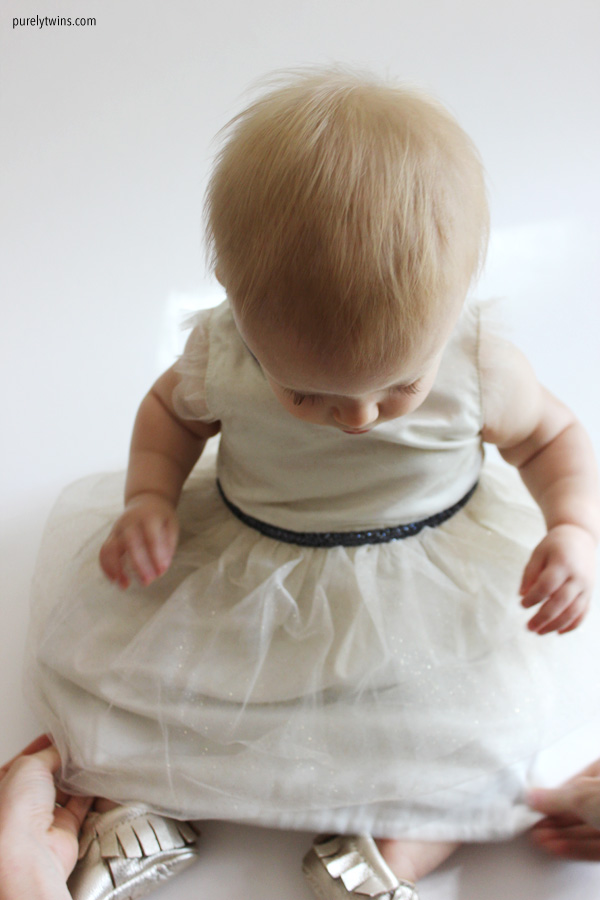 mom-dressing-baby-girl-11-months-old