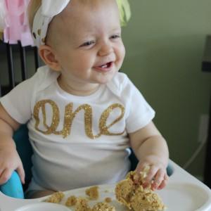 One year old birthday girl enjoying her first birthday cake in her pink and gold birthday outfit. // www.purelytwins.com
