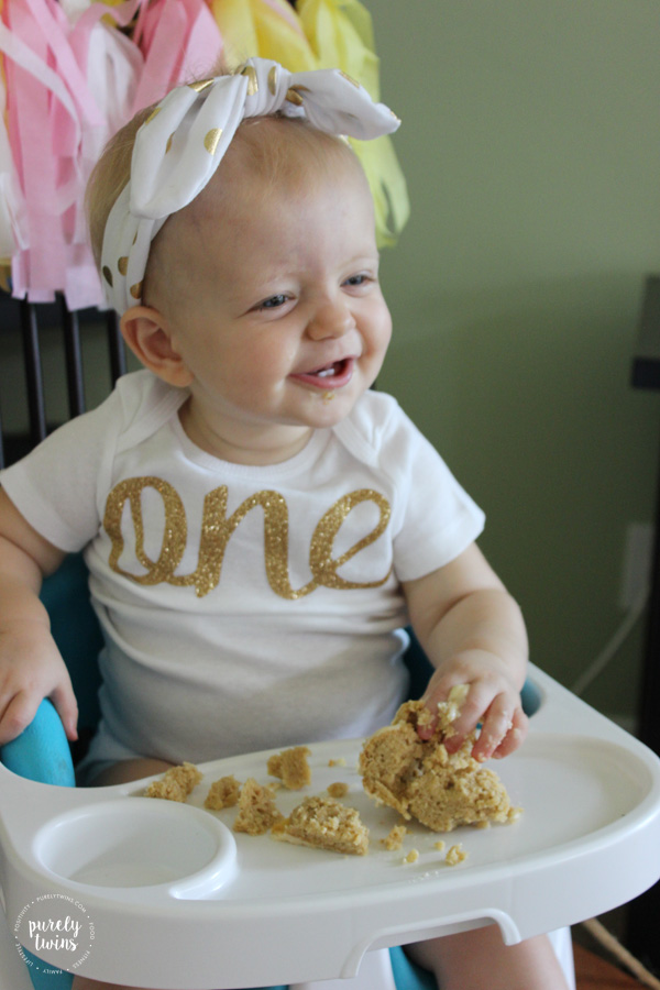One year old birthday girl enjoying her first birthday cake in her pink and gold birthday outfit. // www.purelytwins.com
