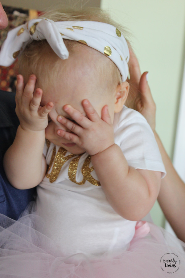 baby girl covering he face on her first birthday party // www.purelytwins.com