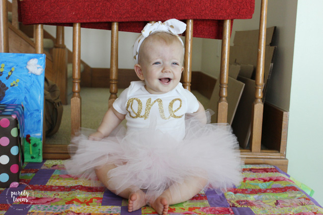 baby girl smiling in her pink and gold birthday onsie outfit with knotted headband and soft pink tutu from bespokedCo off Esty //www.purelytwins.com