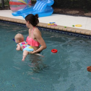 mom-holding-one-year-old-swimming-in-pool-purelytwins