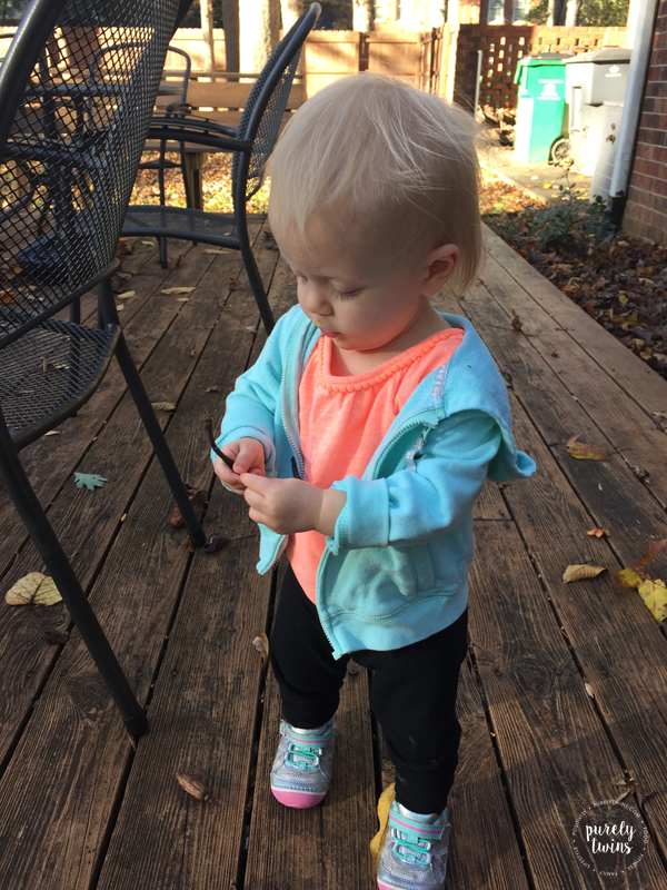13 month old baby girl playing outside in fall in carters jacket