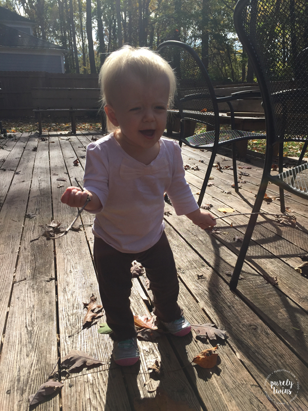 13-month-old-holding-sticks-outside