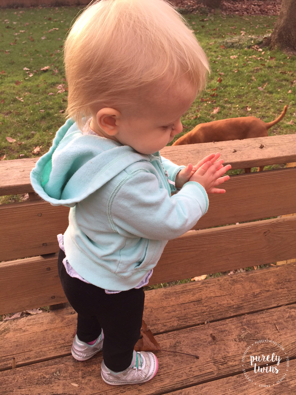 14-month-old-baby-girl-clapping-hands-while-playing-outside