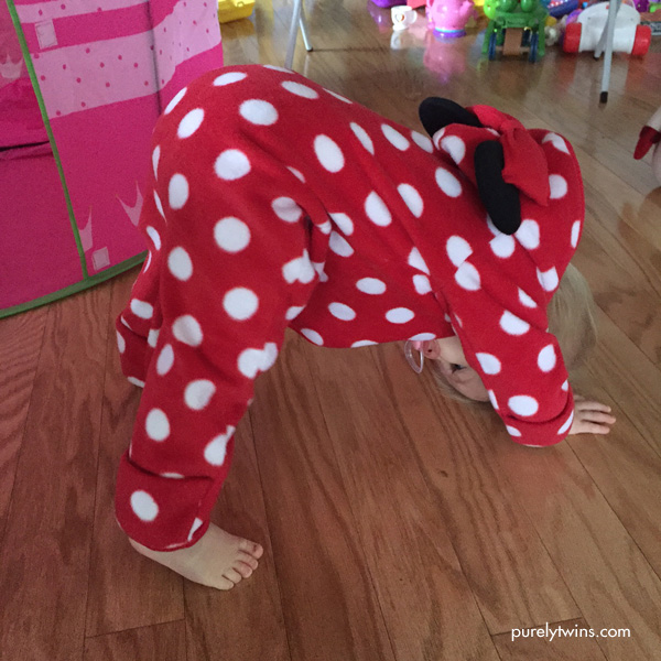 Baby doing downward dog in a minnie mouse outfit