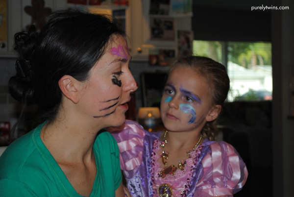 5 year old putting face paint on her aunt.