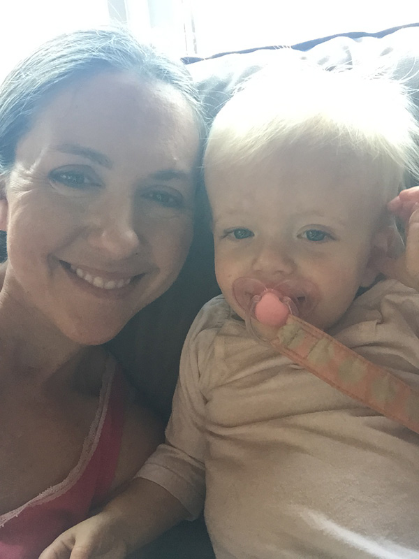 Mom and daughter selfie time on the sofa while snuggling together.