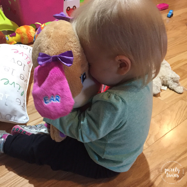 Toddler hugging stuffed animal toy