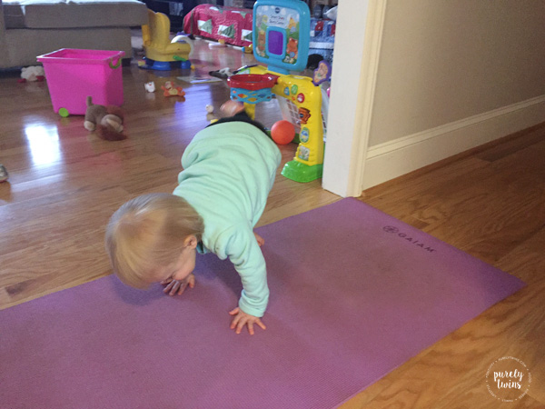Toddler girl doing one leg downward dog.