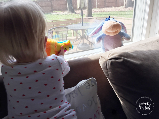 17 month old playing with her stuffed animals next to the window.