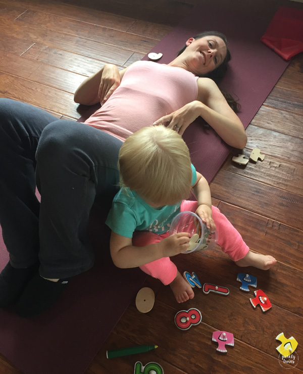 Mom trying to do core workout while her toddler sits next to her.