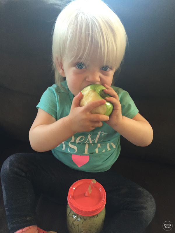Toddler eating apple and green smoothie