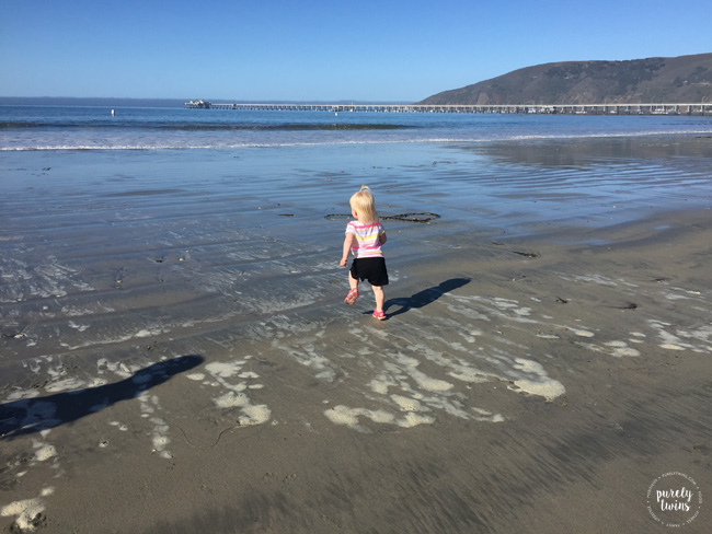 Toddler girl running at beach.