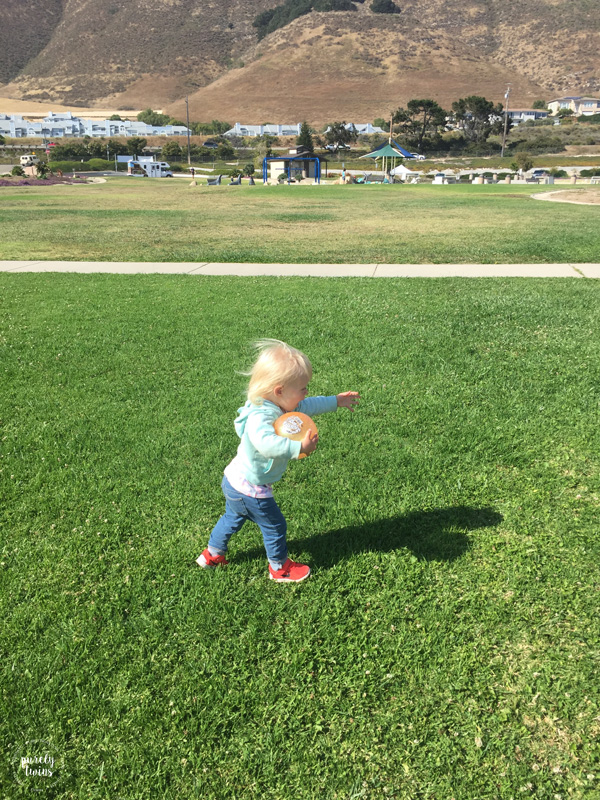 Toddler girl running at park.