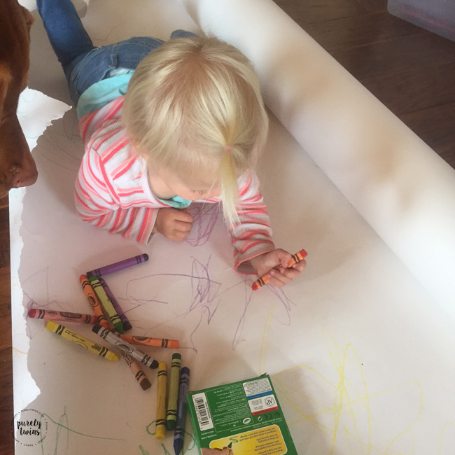 2 year old toddler girl using washable crayons to draw.