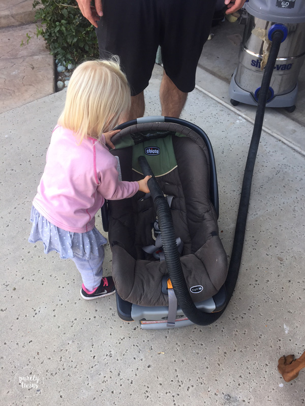 2 year old big sister helping dad clean baby sister's car seat.