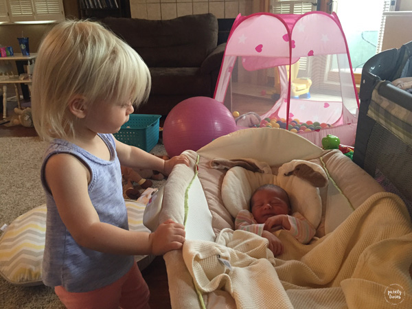 Big sister looking over newborn siste
