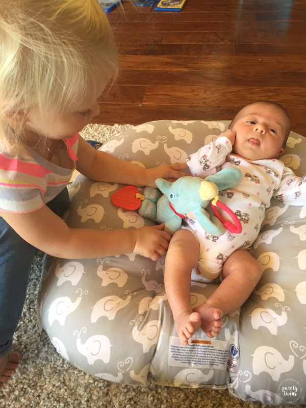 Older sister giving new baby a toy
