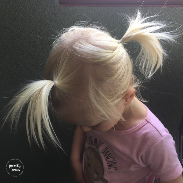 2 year old girl wearing 2 pigtails to help hold back her hair.