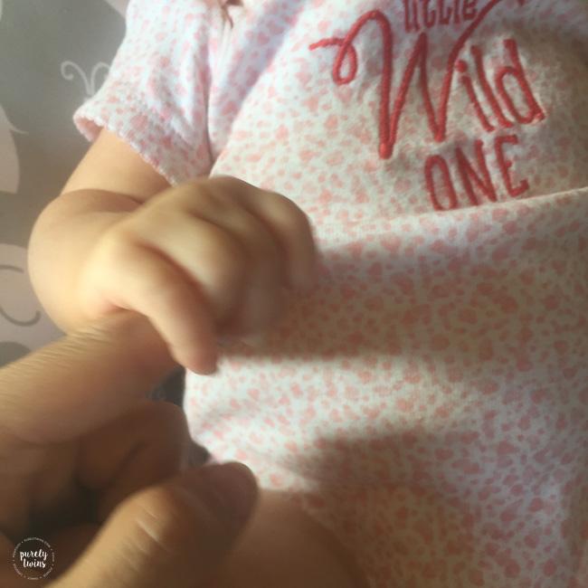 Baby girl holding moms finger at 7 weeks old.
