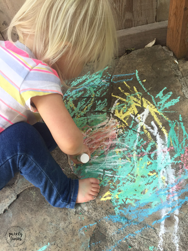2 year old toddler using outdoor chalk to draw.