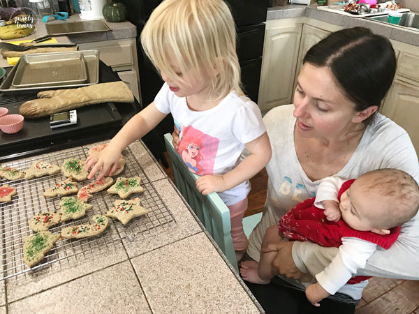 Mom in kitchen with her two daughters making Christmas cookies