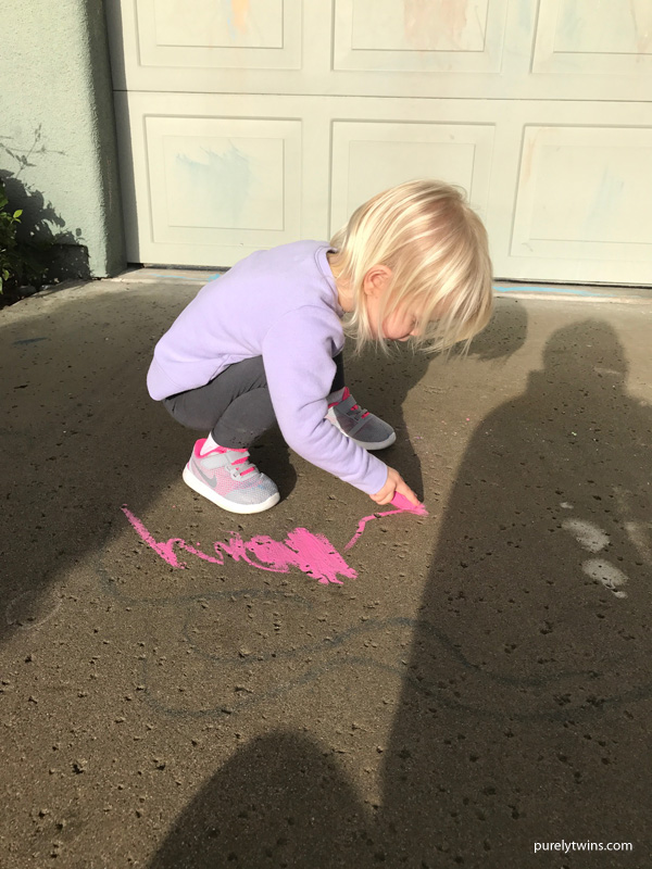 2 years old girl drawing on driveway
