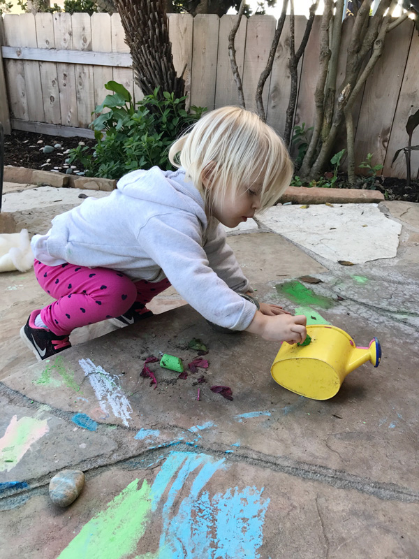 2-year-old-playing-with-chalk-outside-in-california