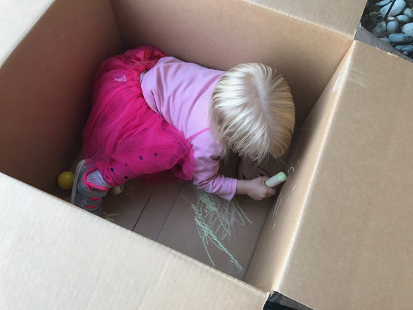 Toddler coloring in a card board box