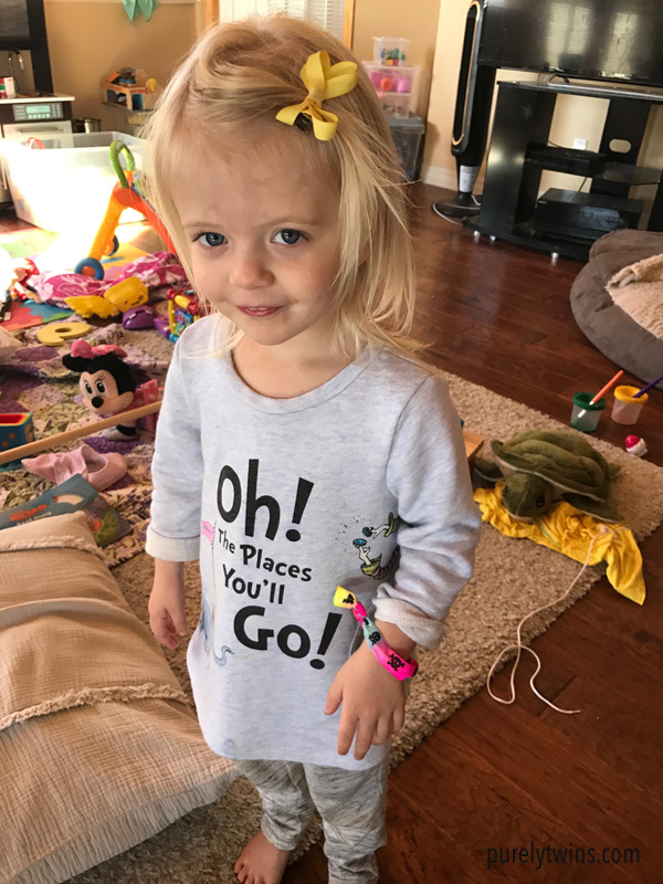 2 and half year old playing dress up with hair tie and hair clip.