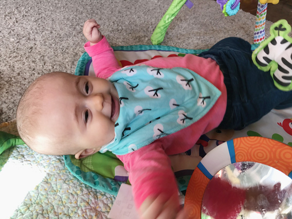 5 month old baby laughing while playing on play mat