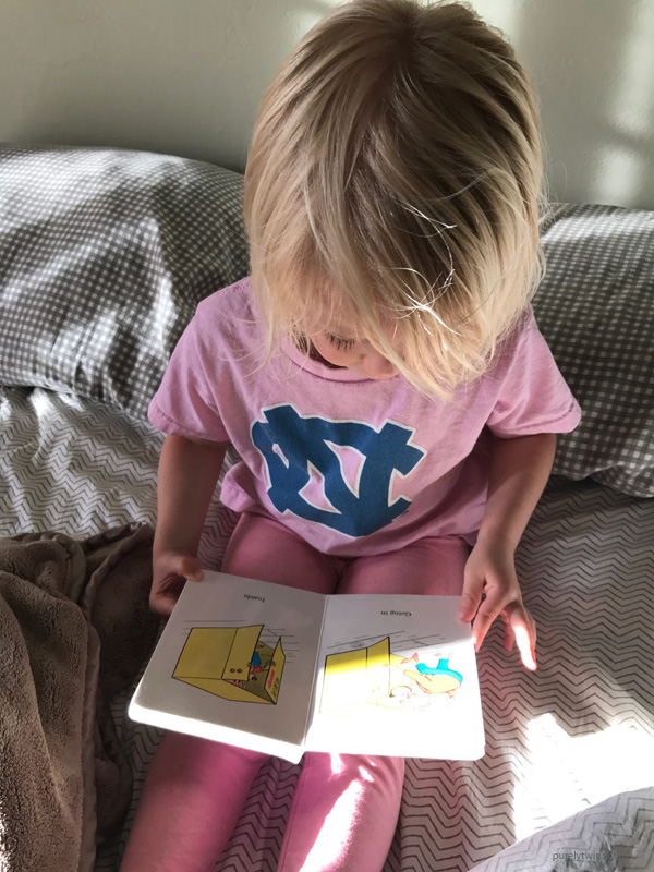 2 1/2 year old girl reading a book