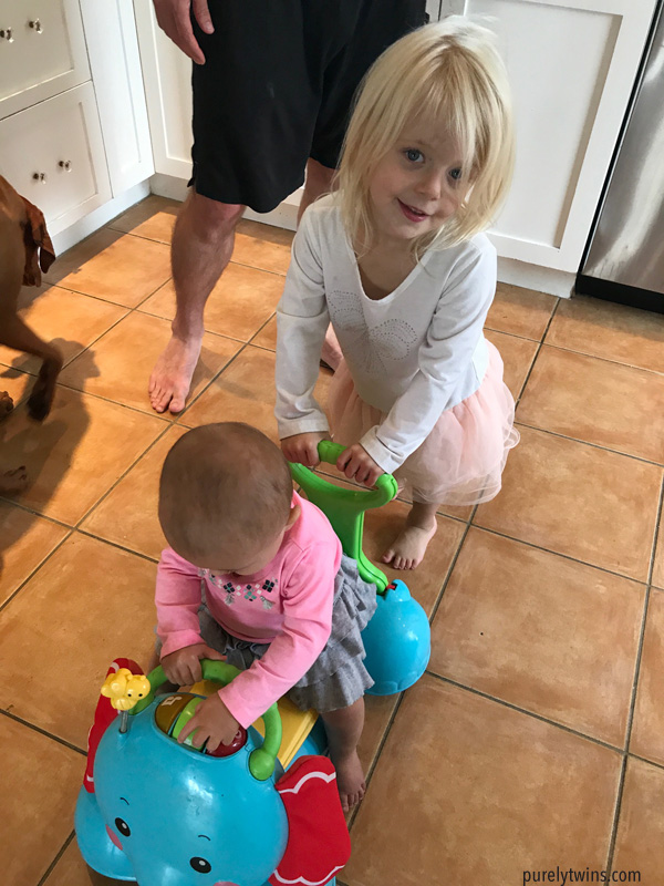 older sister pushing little sis on toy