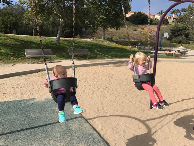 twin sisters swinging together at a park in CA