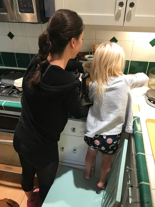aunt and niece making food in kitchen