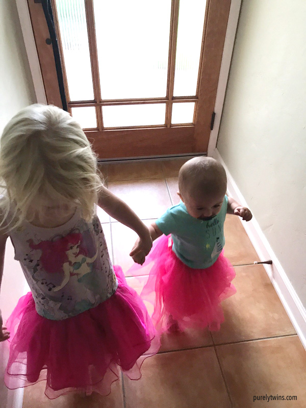 Sisters holding hands where tutus